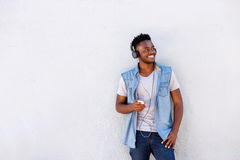Cool african guy with mobile phone and headphones listening to music Royalty Free Stock Image