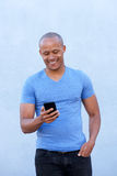 Cool african guy smiling with cellphone. Portrait of cool african guy smiling with cellphone Royalty Free Stock Photo
