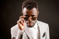 Cool African guy wearing sunglasses looking through them royalty free stock image