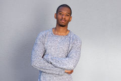 Cool african man standing by gray background with arms crossed. Portrait of cool african man standing by gray background with arms crossed Stock Photography