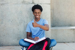 Cool african young adult male student showing thumb up Royalty Free Stock Image