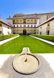 A cool Alhambra Palace fountain and pool. geanada. A cool Alhambra Palace courtyard, fountain and pool reflecting the blue sky of a hot summer's day.  The Stock Image