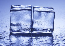 Cool as ice. Two ice cubes backlit with droplets stock image