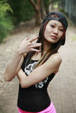 Cool Asian girl looking at viewer. Cool Asian girl with hip hop hand gestures Stock Photo