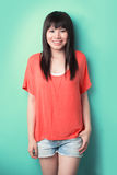 Cool Asian woman leaning against a wall. Royalty Free Stock Image