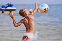 Cool sports boy jumping on the ball at sea