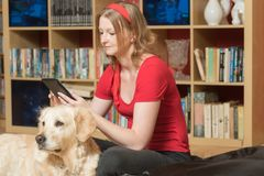 Relaxing with a dog and looking at the tablet stock images