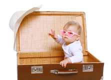 Cool baby in sunglasses playing in suitcase Stock Image