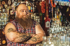Cool bearded bartender situating in tap-room Royalty Free Stock Photos