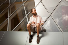 Cool bearded tattooed guy posing in front of office building. Modern start up company Stock Photos