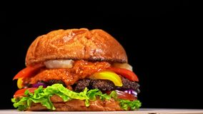 Cool beautiful fresh juicy cooked burger rotate on turntable. Very luscious air bun and marbled beef. Restaurant where. Each burgers is cooked by hand. Not made stock video footage
