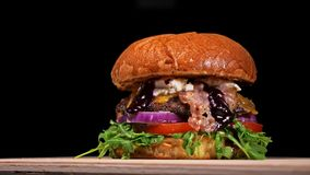 Cool beautiful fresh juicy cooked burger rotate on turntable. Very luscious air bun and marbled beef. Restaurant where. Each burgers is cooked by hand. Not made stock footage