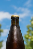 Cool beer bottle by a blue sky. Closeup of a cool beer bottle top by a blue sky Stock Photography