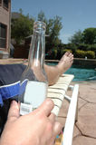 Cool Beer by the Pool. Man holds beer bottle as he lays out in the sun by the pool Stock Photo