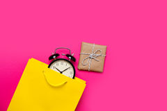 Cool black alarm clock in beautiful yellow shopping bag and cute Royalty Free Stock Image