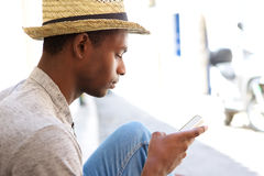 Cool black guy looking at mobile phone Royalty Free Stock Photography