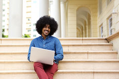 Cool black guy sitting outside using laptop Royalty Free Stock Photos