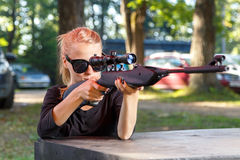 Cool blond in sun glasses aiming from telescopic gun Stock Photos