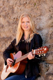 Cool blonde girl playing guitar outdoor Stock Images