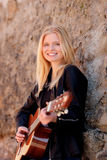 Cool blonde girl playing guitar outdoor Royalty Free Stock Image