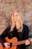 Cool blonde girl playing guitar outdoor Royalty Free Stock Photos