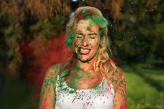 Cool blonde girl wearing white shirt and posing covered with dry paint at the Holi Festival. Cool blonde woman wearing white shirt and posing covered with dry stock images