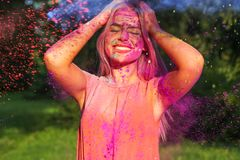 Cool blonde model with long hair covered purple dry paint celebrating Holi festival. Cool blonde woman with long hair covered purple dry paint celebrating Holi stock photos