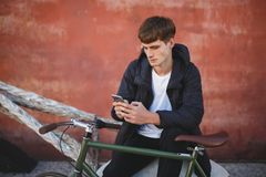 Cool boy with brown hair sitting and using his cellphone. Young man in down jacket and white t-shirt sitting with mobile. Cool guy with brown hair sitting and Stock Photography
