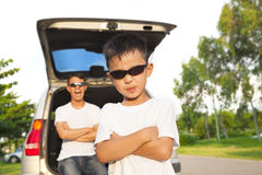 Cool boy and father across arms with their car stock image