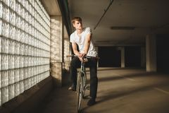 Cool boy riding classic bicycle while dreamily looking aside. Young thoughtful man in white t-shirt standing with. Portrait of cool boy riding classic bicycle Stock Photography