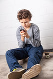 Cool Boy sitting on his skateboard, holding a smartphone Stock Images