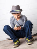 Cool Boy sitting on his skateboard, holding a smartphone Royalty Free Stock Photo