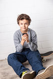 Cool Boy sitting on his skateboard, holding a smartphone Royalty Free Stock Image