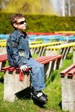 Cool boy sitting in a park. Cool and trendy boy sitting on a bench in a park Stock Image