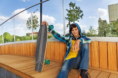Cool boy with skateboard sits in park Stock Photos