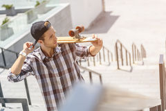 Cool boy with skateboard on steps. Pensive male skateboarder is standing on stairs with skate. Man is touching his cap and looking forward with confidence Stock Images