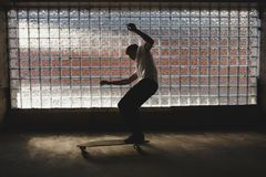 Cool boy that skateboarding and making tricks with glass wall on background. Young man in white t-shirt trying to make stock image