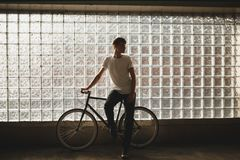 Cool boy standing with classic bicycle and dreamily looking aside posing on camera. Young thoughtful man in white t. Cool boy standing with classic bicycle and Royalty Free Stock Images