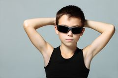 Cool boy. In sunglasses with hands on his head on grey background Royalty Free Stock Images
