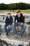 Cool boys sitting on a stone. At the skate park stock photos