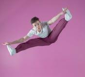 Cool break dancer mid air doing the splits. In the dance studio Stock Photos