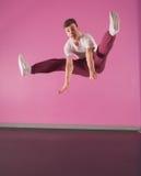Cool break dancer mid air doing the splits. In the dance studio Stock Photo