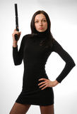 Cool brunette in close black with gun Stock Photos