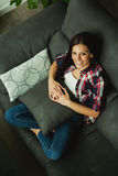 Cool brunette girl sitting on the sofa Stock Photography