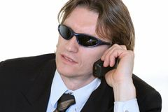 Cool Business Man. Business man with sung glasses talkingon cell phone Stock Images