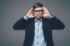 Cool businessman with hands on head standing on grey background Stock Photography