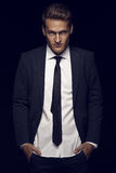 Cool businessman standing on dark background Stock Images