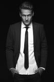 Cool businessman standing on dark background Stock Photos