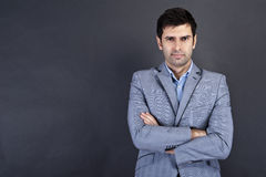 Cool businessman standing on grey background Royalty Free Stock Photography