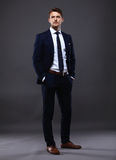 Cool businessman standing on grey Royalty Free Stock Photography